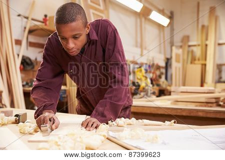 Apprentice Planing Wood In Carpentry Workshop