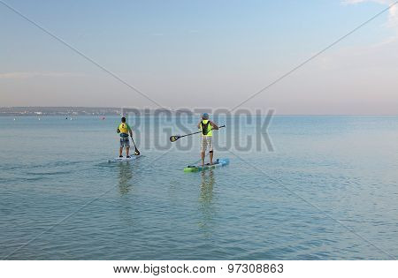 Two Paddle Board Surfers At Dawn