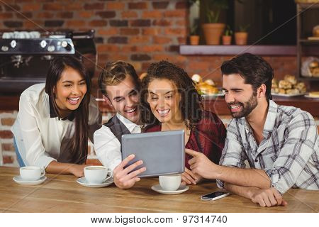 Smiling friends looking at digital tablet at the coffee shop