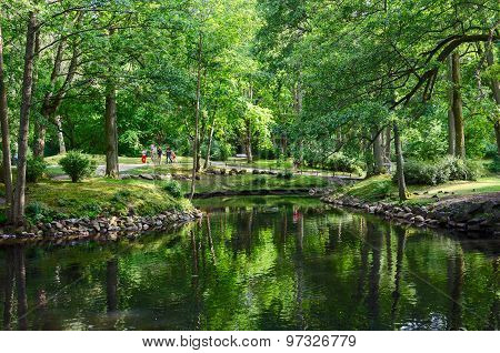 Lithuania, Palanga. People Walk In The Botanical Park Near Pond