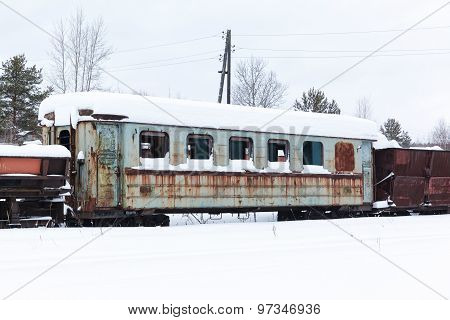 Abandoned rusty wagons on narrow-gauge railway under the snow