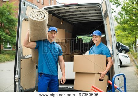Workers Carrying Carpet And Cardboard Boxes