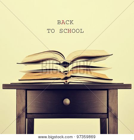 some open books on a table and the sentence back to school on a beige background, with a retro effect