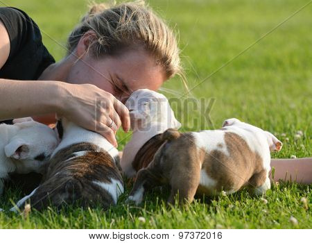 woman laying in the grass playing with litter of bulldog puppies
