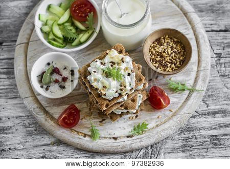 Healthy Snack - Rye Crackers, Cottage Cheese With Cucumber And Flax Seed On A Light Wooden Backgroun