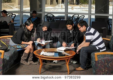 Ethnically diverse group of students studying inside campus building