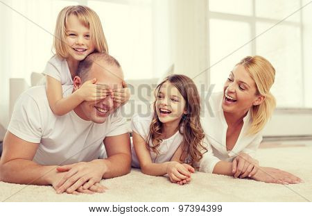 family, children and home concept - smiling family with and two little girls lying on floor at home and having fun
