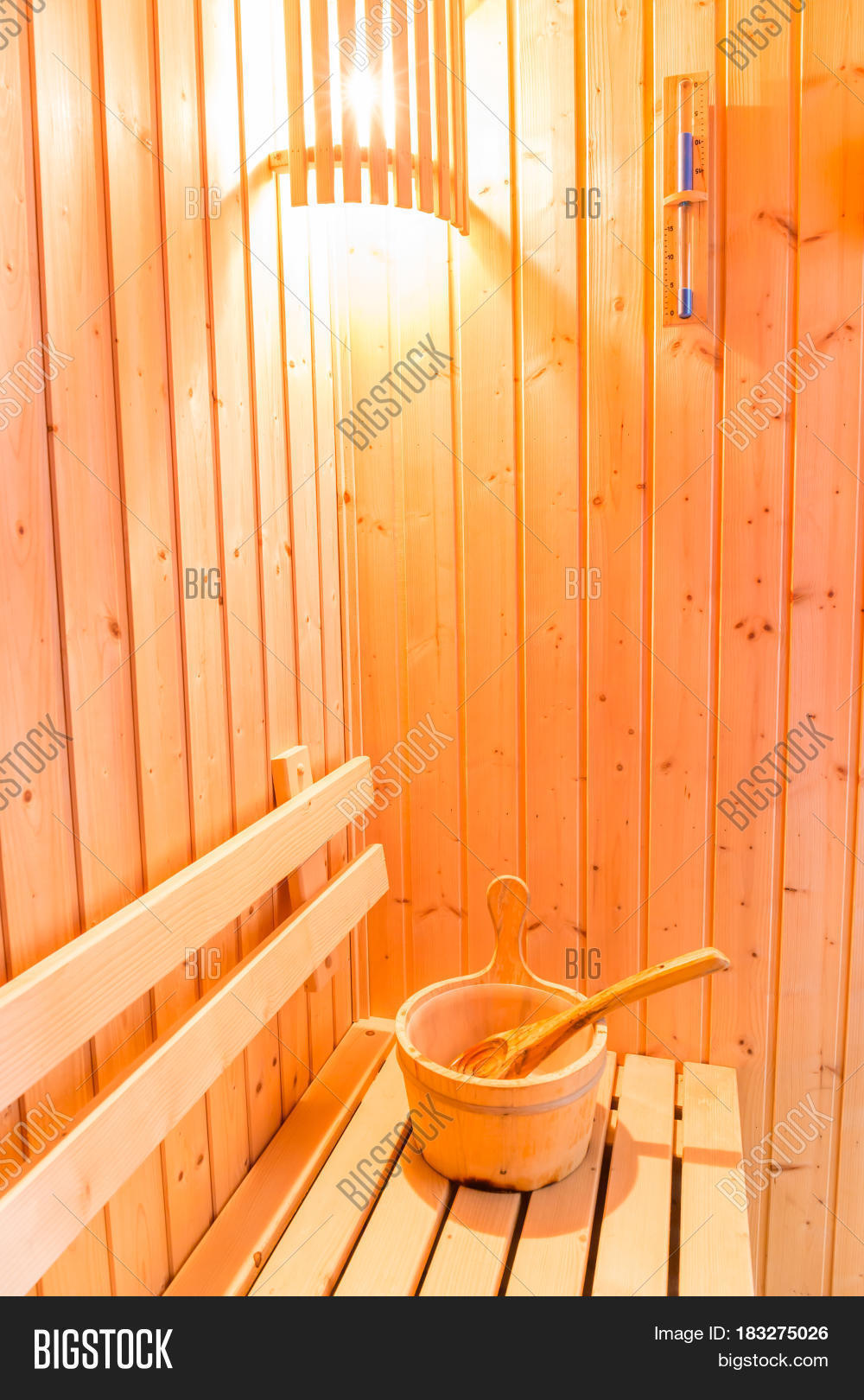 Sauna accessories in sauna room wooden bucket place on bench and sand clock timer on wooden wall.