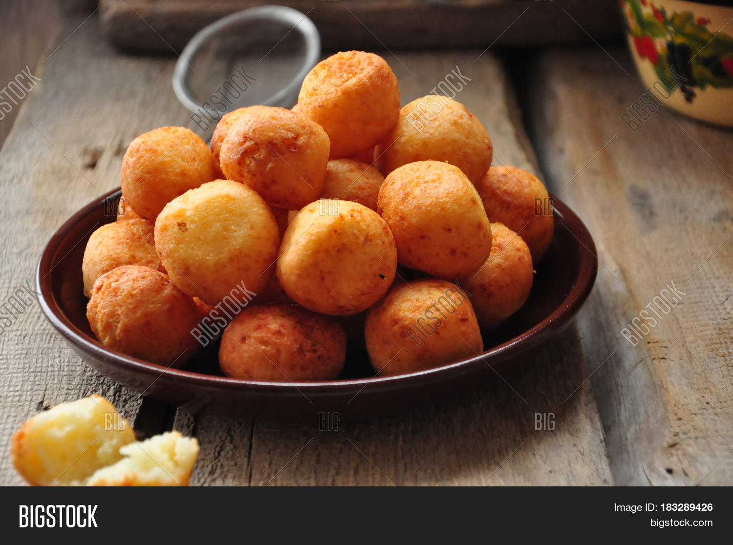 Small balls of freshly baked homemade cottage cheese doughnuts in a plate on a wooden background. Rustic style.