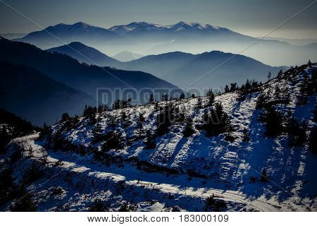 Winter mountain ridges under the setting sun and a road passing by