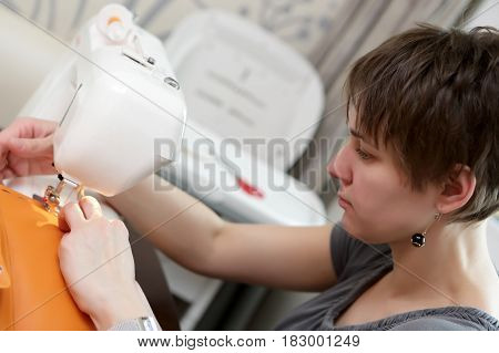 Woman using a sewing machine at home