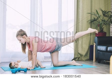 Mother And Little Toddler Doing Fitness At Home On An Exercise Mat Together And Smiling