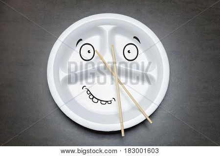 Empty disposable plastic plate on black table. White plate with three sections for food with spoon and bamboo chopsticks. Happy smiley drawn face on dish plate