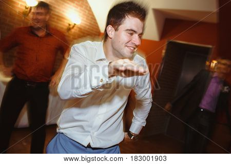Crazy dances of the cheerful groom on the wedding party