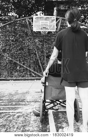 Woman Holding Wheel Chair  With With Sitting Man At Basketball Court