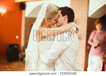 Passionate Kiss Of The Newlyweds On The Wedding Party