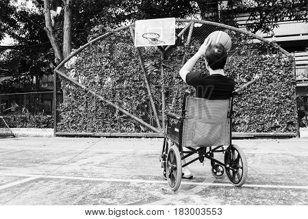 Man Sitting On Wheel Chair With Broken Leg In Plaster Cast , Try To Shoot Basketball  At Court