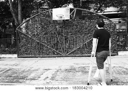 man standing with broken leg in Plaster cast using Crutches at basketball court in white tone