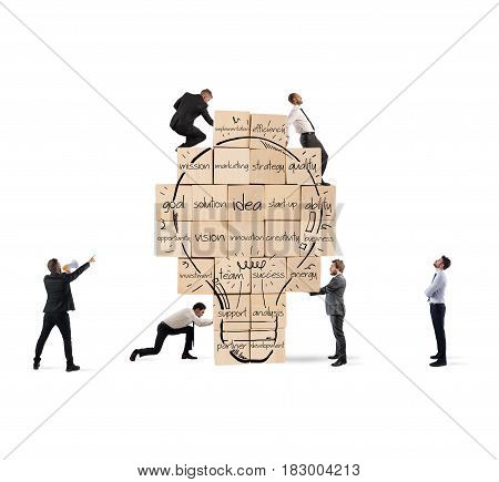 Business person built together a big brick wall with drawn lightbulb with business terms. Concept of creating a new idea.