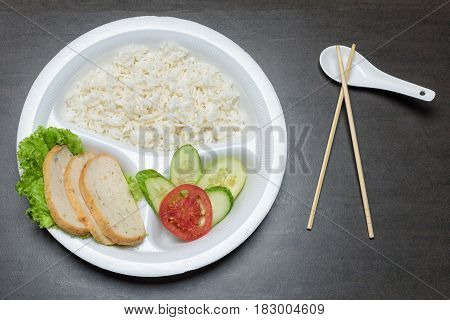Disposable plastic food plate on black table. White plate with rice meat and vegetables. Spoon and bamboo chopsticks. Healthy take-away concept