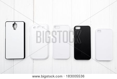 Blank printing Cases for cell phones lying in raw, all sized-matched, black and white, topview