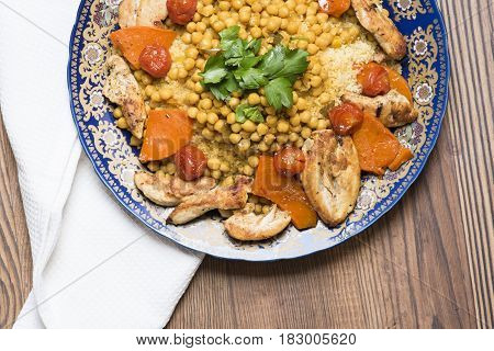Arabic recipe with couscous, vegetable and chicken meat served on a porcelain plate