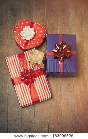 photo of beautiful cute gifts of different shapes on the wonderful wooden background