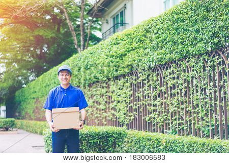 Delivery concept - Smiling happy young asian handsome male postal delivery courier man in front of house delivering package carrying box with service mind and blue uniform