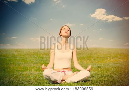 Photo Of Beautiful Young Woman Doing Joga And Relaxing On The Wonderful Field Background