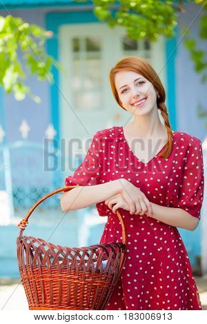 Portrait Of Beautiful Young Woman With Basket On The Wonderful Trees And Building Background