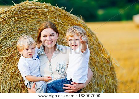 Happy family enjoying sunset in wheat field. Beautiful young woman with two adorable toddler kids boys. Mother holding two children, twins on arms on meadow on a sunny evening. Mom and sons. Outdoors.