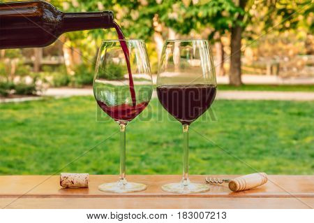 Red wine poured from a bottle into a glass at a picnic, with a cork and a corkscrew, with green grass in the blurred background, on a sunny day