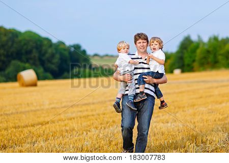 Happy family enjoying sunset in wheat field. Beautiful young man with two adorable toddler kids boys. Father holding two children, twins on arms on meadow on a sunny evening. Dad and sons. Outdoors.