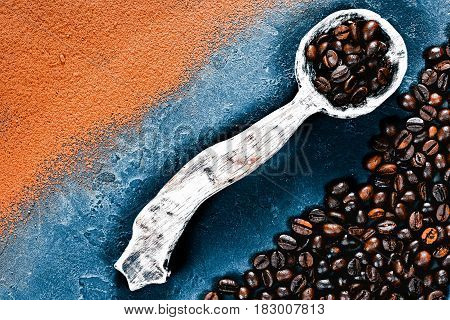 Cocoa powder and coffee beans scattered and partly covering black slate background. Rustic wooden spoon full of coffee beans. Top view