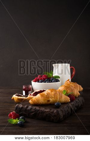 Fresh croissants and ripe berries on old wooden background. Healthy breakfast concept with copy space. Dark photo.