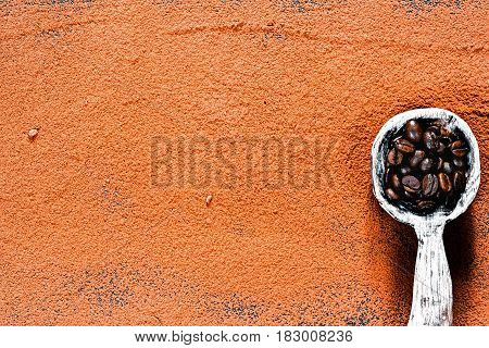 Cocoa powder scattered as background. Rustic wooden spoon full of coffee beans. Top view