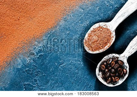 Cocoa powder scattered and partly covering black slate background. Rustic wooden spoons full of cacao powder and coffee beans. Top view