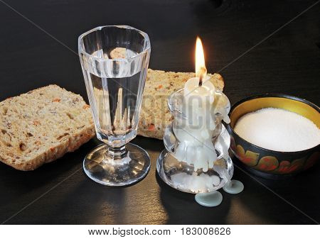 Closeup view of vintage shot glass for vodka fresh bread bun beautiful vintage saltcellar and glass candlestick with a burning candle on black wooden table.