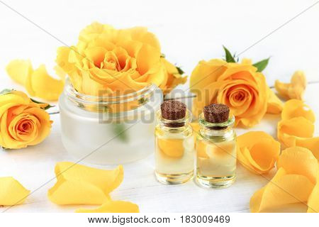 Rose essential oil for aromatherapy and beauty treatment. Extract in bottles, yellow petals, cosmetic jar with flower.