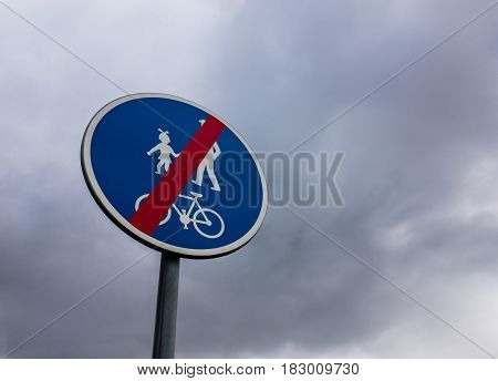 End of bicycle zone sign against cloudy sky