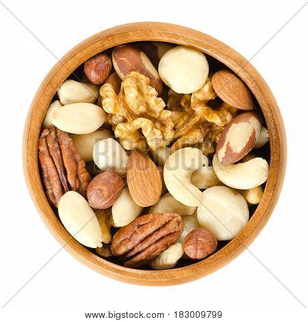 Raw mixed nuts in wooden bowl. Dried walnuts, hazelnuts, almonds, cashews, macadamia, Brazil and pecan nuts. Fancy mix of snack food. Isolated macro food photo close up from above on white background.