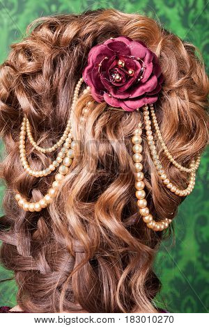 Beautiful hairstyle from behind on green background in retro interior. Rococo period. Luxury and high class