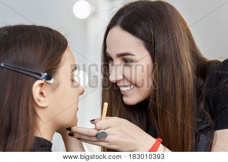 happy makeup artist doing makeup for young girl.  Make-up artist work in studio. Real people. Backstage photo as visagiste applying makeup
