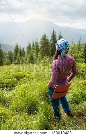 woman tourist admiring views of the mountains. Hiker girl enjoying beautiful mountain view. Tourist in the mountains. Healthy lifestyle, adventure, hiking trip