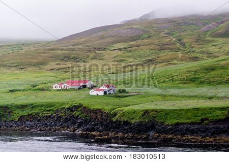 Lonely farmstead in Iceland on a rocky coast in bad weather