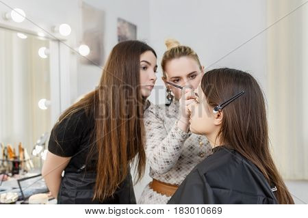 makeup teacher with her student girl. Makeup tutorial lesson at beauty school. Visagiste applying makeup on the eyes. Makeup master class