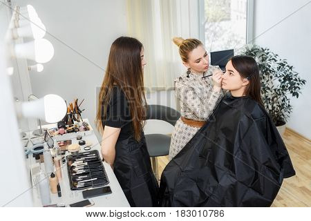 makeup teacher training her student girl to become makeup artist. Makeup lesson at beauty school. Make-up artist work in her studio. Backstage photo as visagiste applying makeup. Makeup master class