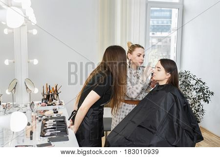 makeup tutorial lesson at beauty school. Makeup teacher training her student girl to become makeup artist. Real people. Portrait of visagiste applying makeup on the eyes. Makeup master class