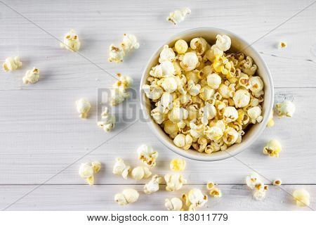 Salty Popcorn In A Blue Cup Is On A Wooden Table. Popcorn Lies Around The Bowl. Top View.