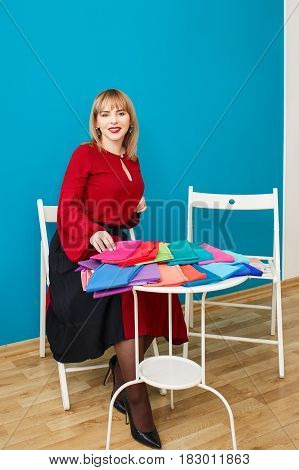 portrait of stylist with set of colorful fabric swatches for color analysis consultation. Color type test. Color-type determination. Image maker ready to work